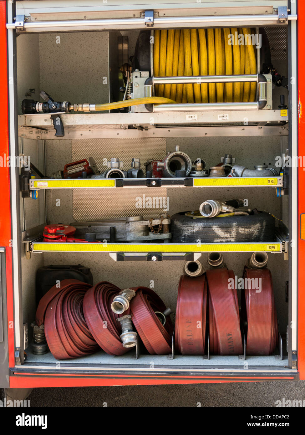 Fire hoses and nozzles inside a fire engine  Derbyshire England Stock Photo