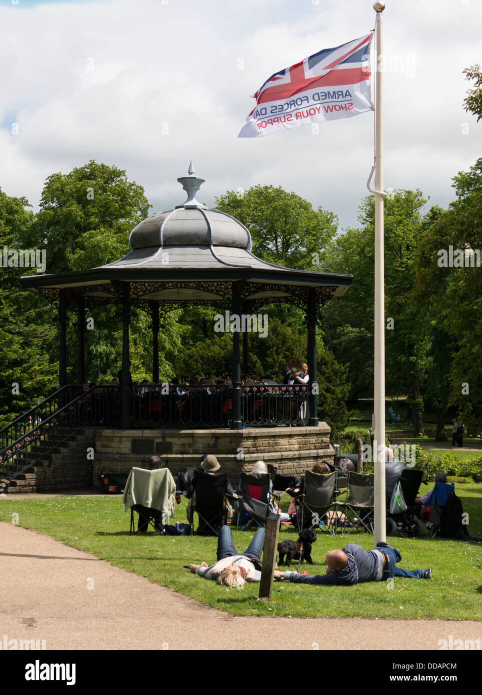 People sitting in front of the Bandstand listening to brass bands  in the Pavilion Gardens Buxton Derbyshire Peak - Stock Image