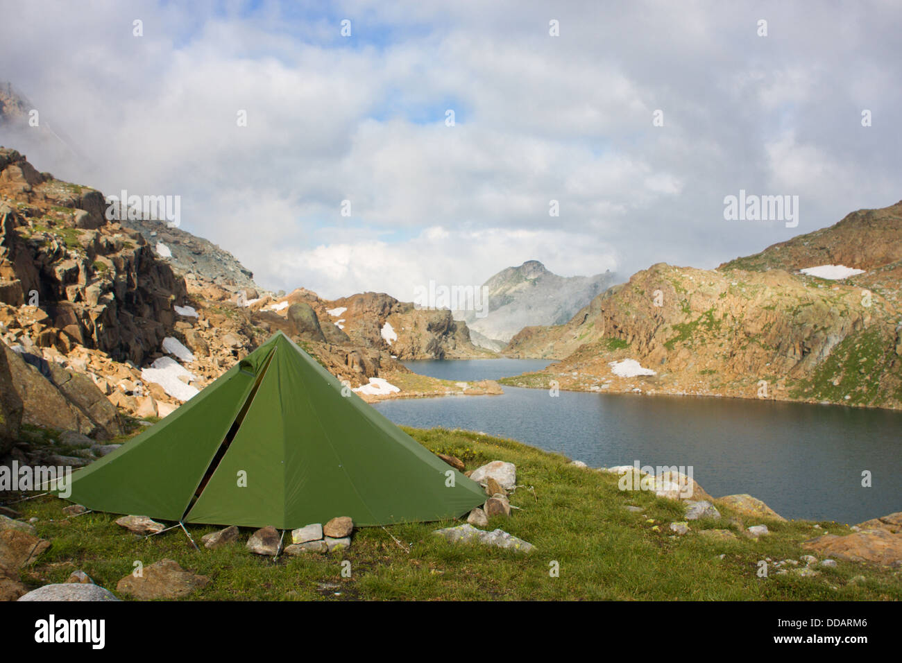 Hiking in the mountains; a green tent near a beautiful mountain lake - Stock Image