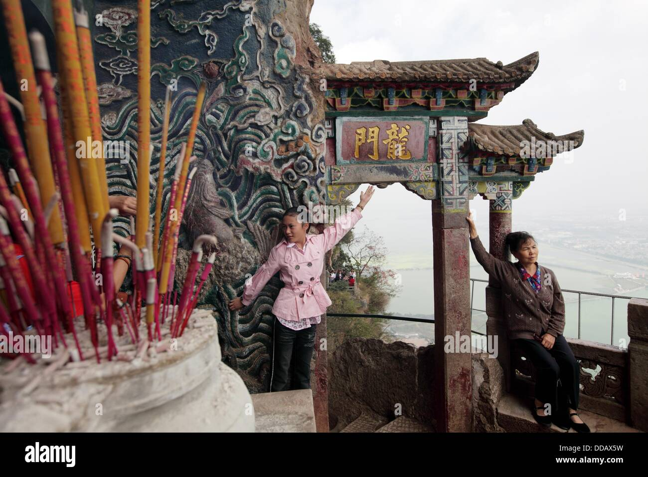 Visitors having photos taken in front of Historical Dragon Gate on Western Mountain over look Dian Lake Dianchi - Stock Image