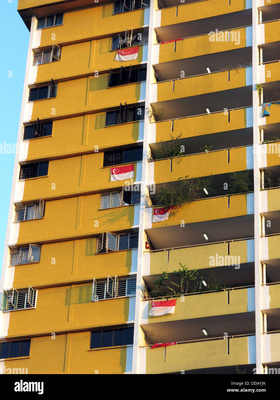 Singaporean flags hang from a Singapore apartment building Stock Photo
