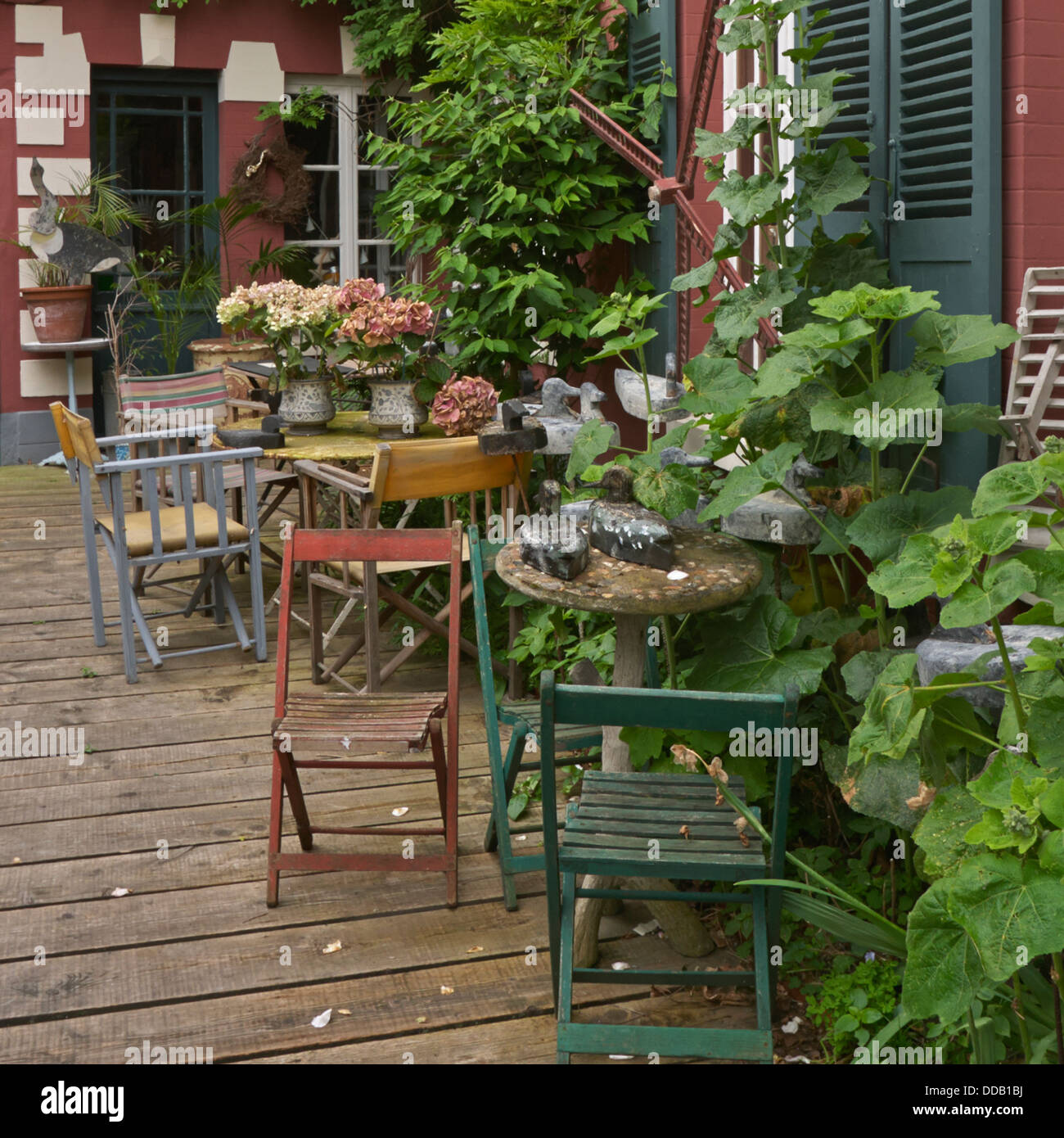 Rustic chairs in muted colours in French courtyard with flowers and foliage - Stock Image