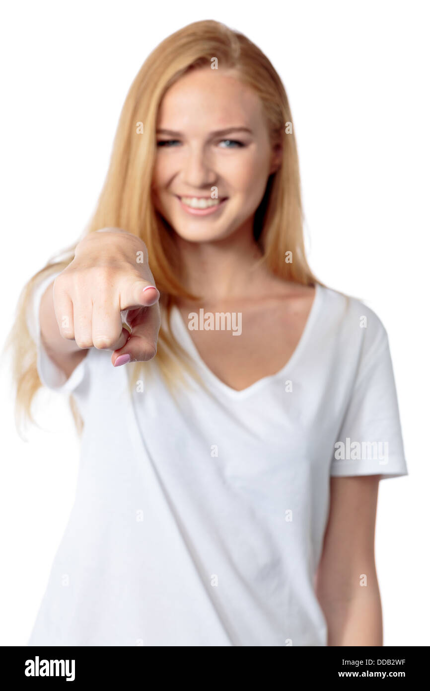 Young woman smiling and pointing at the viewer with her index finger as she makes a choice or identifies a person - Stock Image