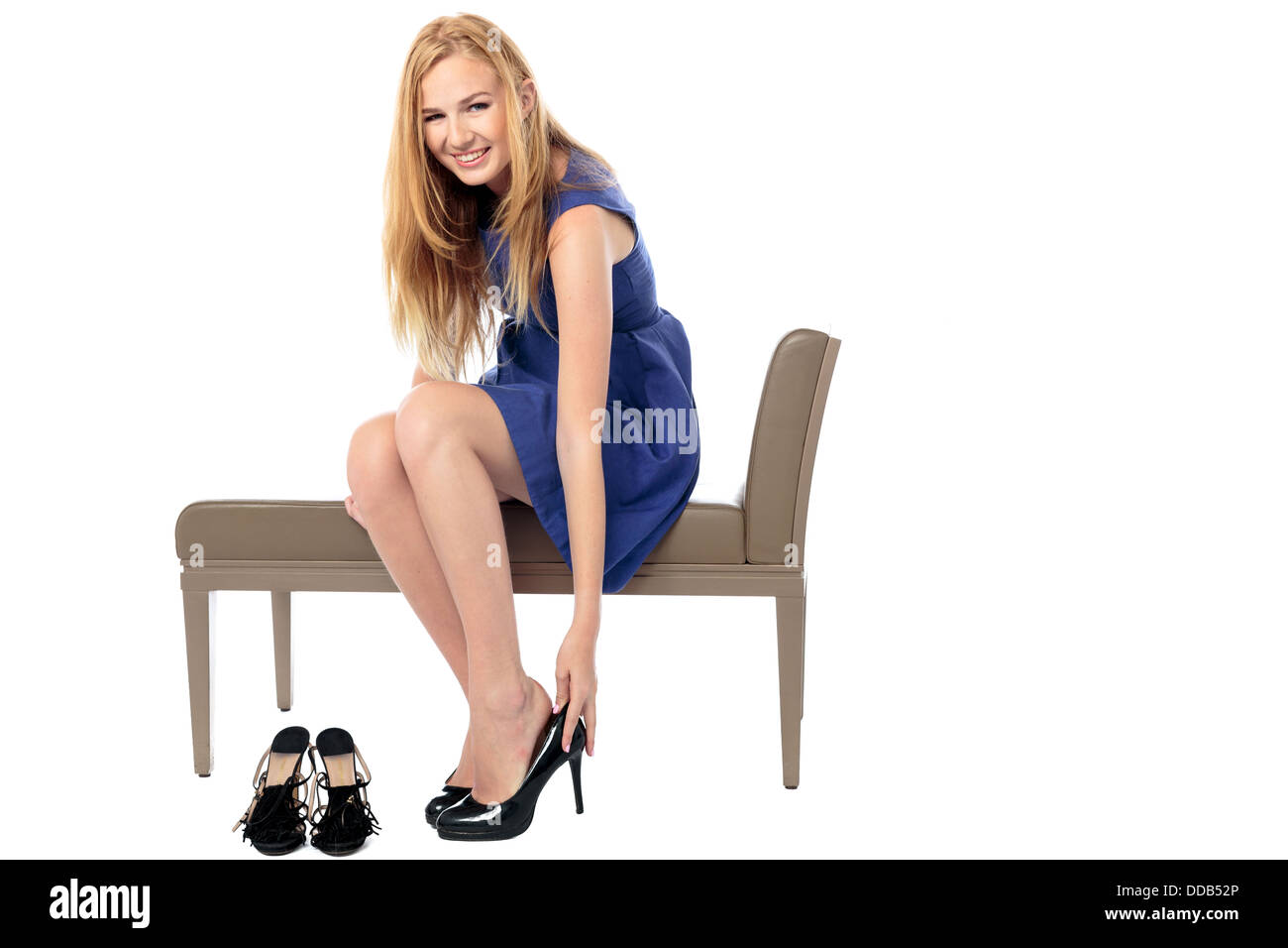 Smiling stylish young woman sitting on a seat putting on her elegant high heeled shoes, isolated on white - Stock Image