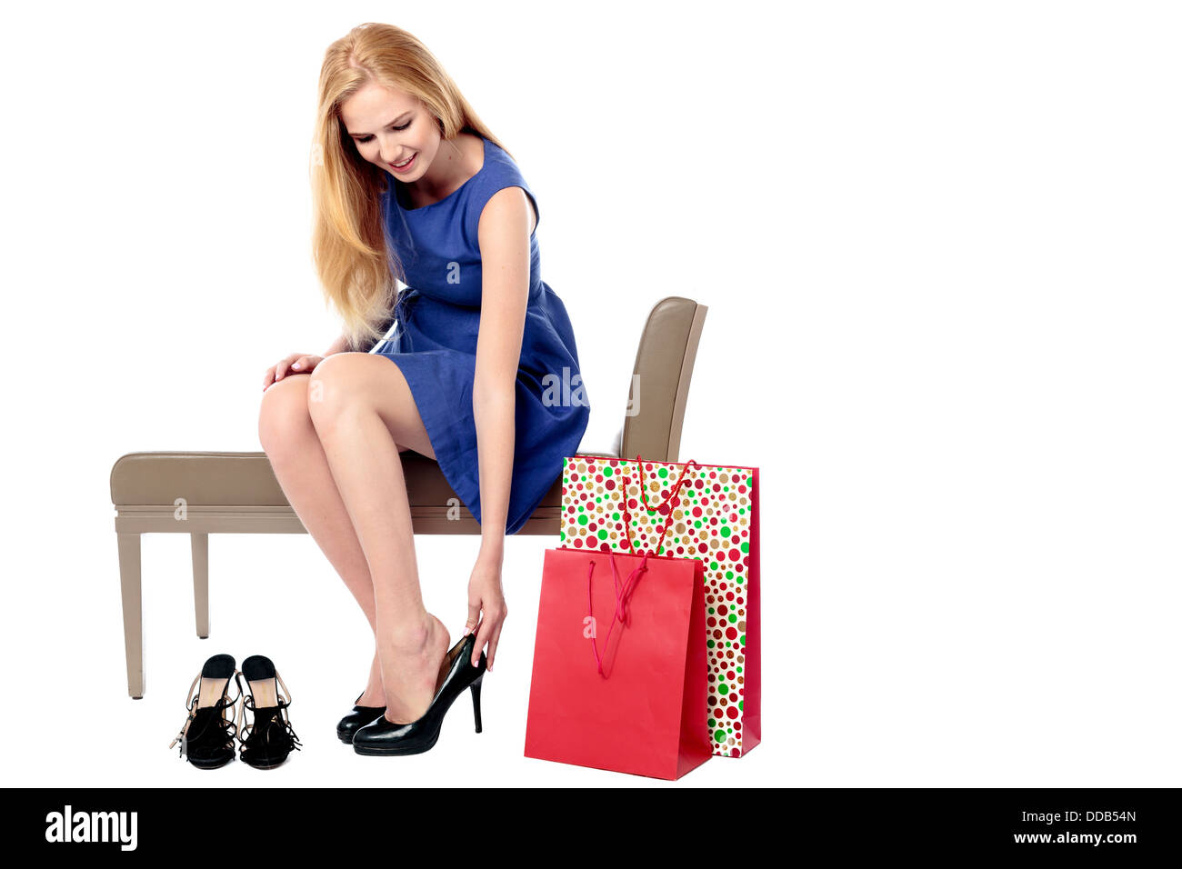 Glamorous young woman trying on a pair of stylish high heel shoes while out shopping in a store with colourful shopping - Stock Image