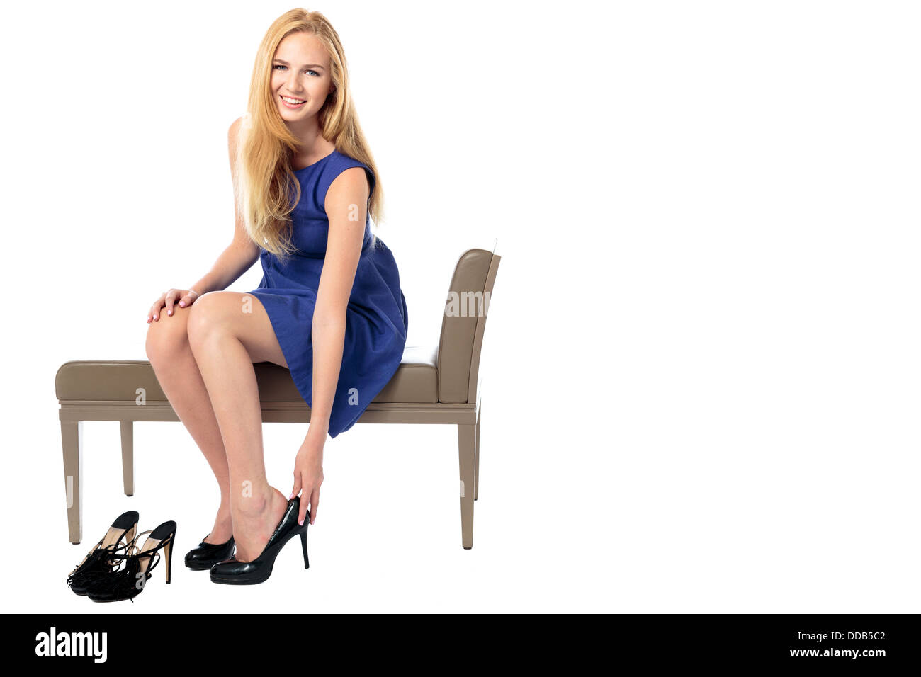 Fashionable beautiful young woman seated on a bench changing her high heeled shoes, isolated on white - Stock Image