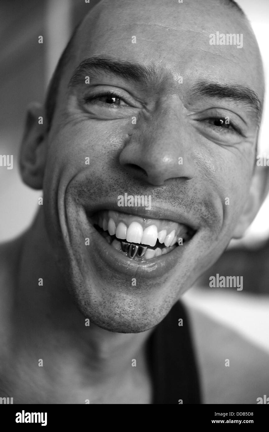 Portrait of young man smiling with 3 gold teeth showing he is former bare knuckle boxer and bouncer James Lambert - Stock Image