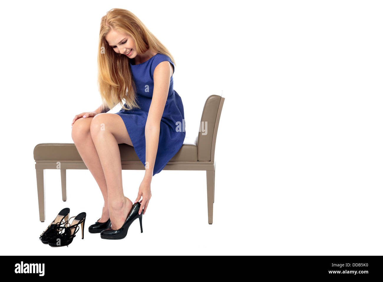 Elegant smiling young woman sitting on a bench changing her shoes for a stylish classical high heeled court shoe, - Stock Image