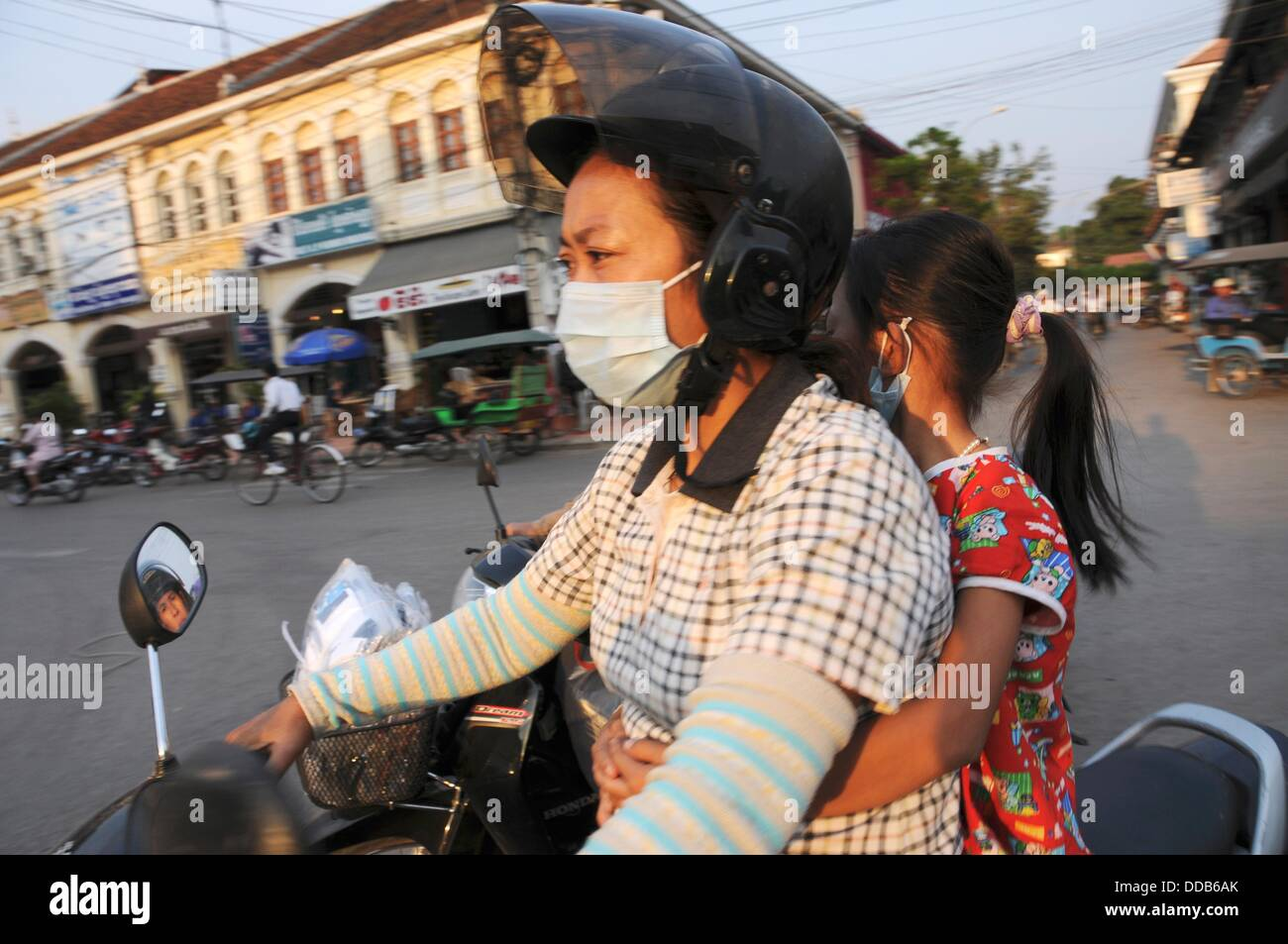 Cambodian Women driving with a helmet, respiratory protection and child on a scooter - Stock Image