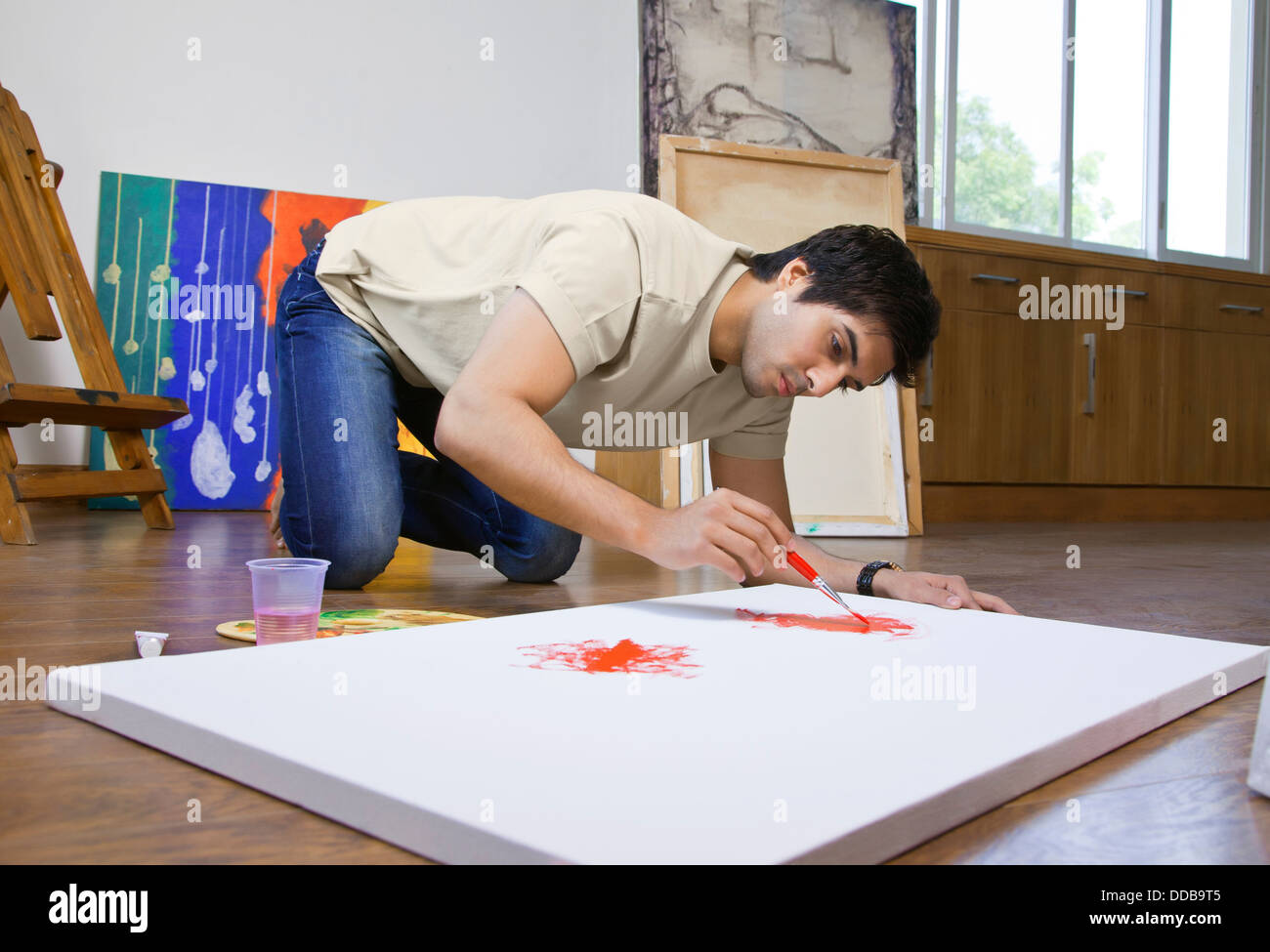 Young man painting on an artist's canvas at art studio - Stock Image
