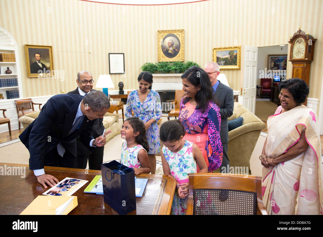 US President Barack Obama talks with departing staff member Ruchi Bhowmik and her family in the Oval Office of the - Stock Image