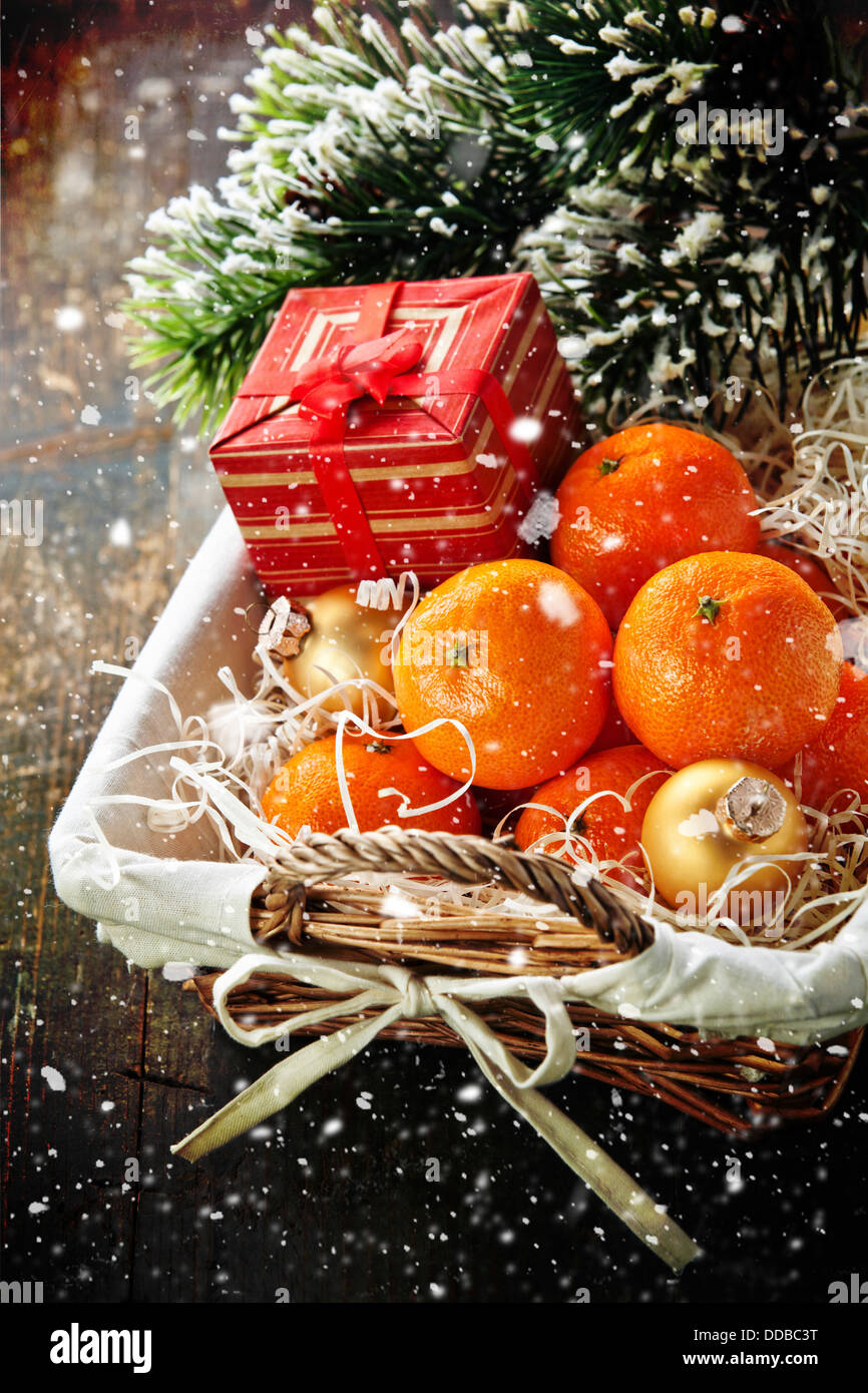 Mandarins in basket with Gift and Christmas tree branch - Stock Image