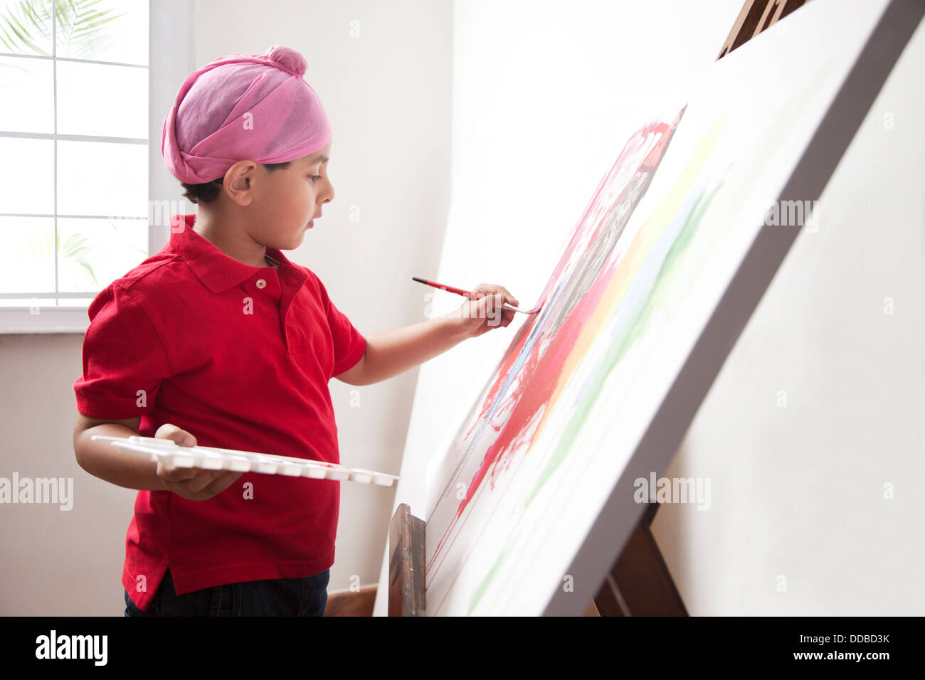 Cute little boy painting on artist's canvas with paintbrush - Stock Image
