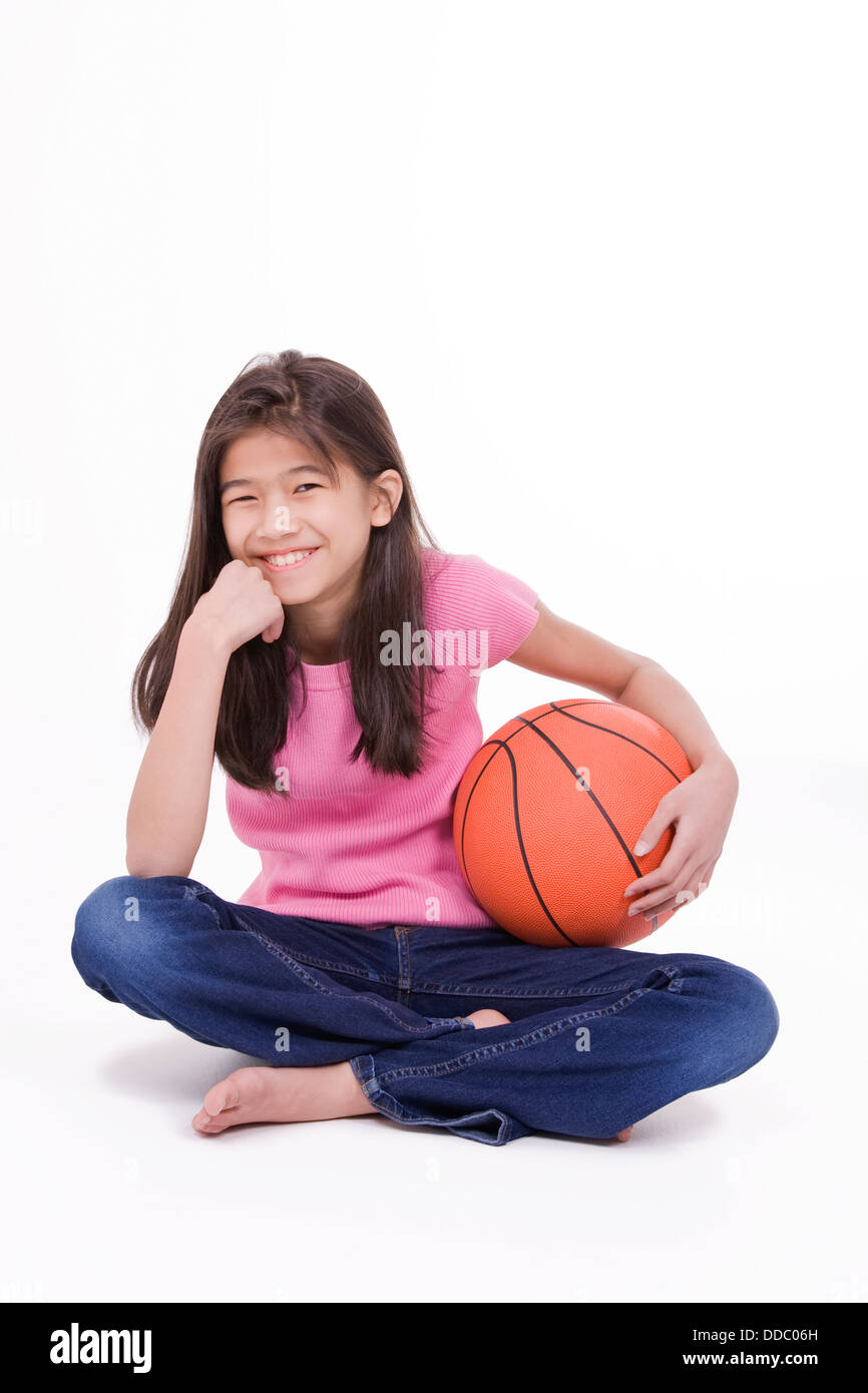Ten year old Asian girl holding basketball, isolated on white - Stock Image