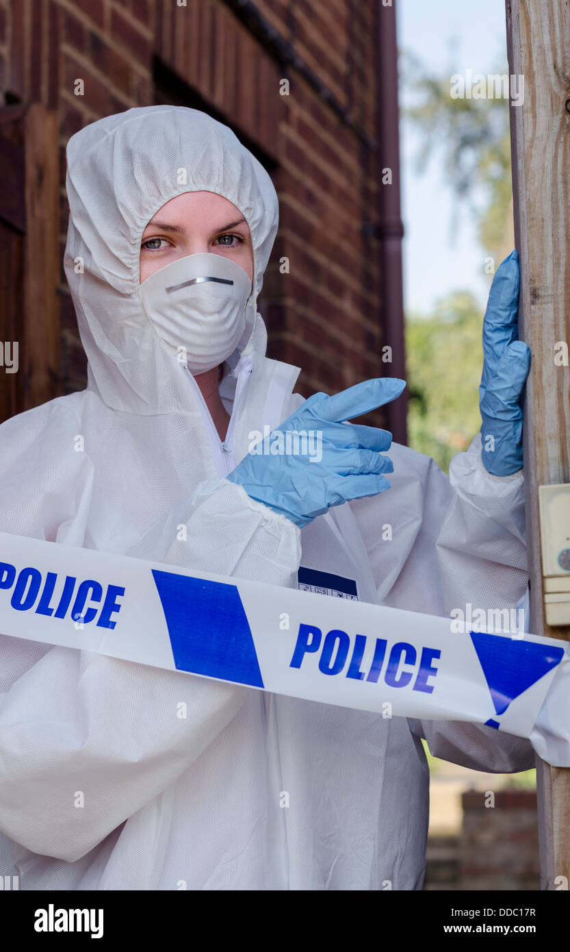 Crime scene investigator behind a police cordon - Stock Image