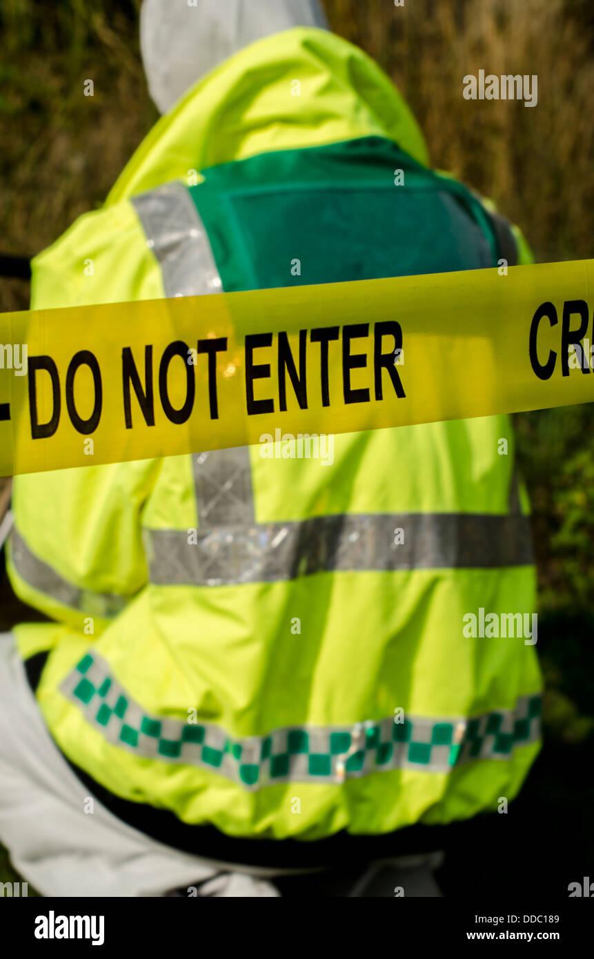 Police officer working behind a crime scene barrier - Stock Image