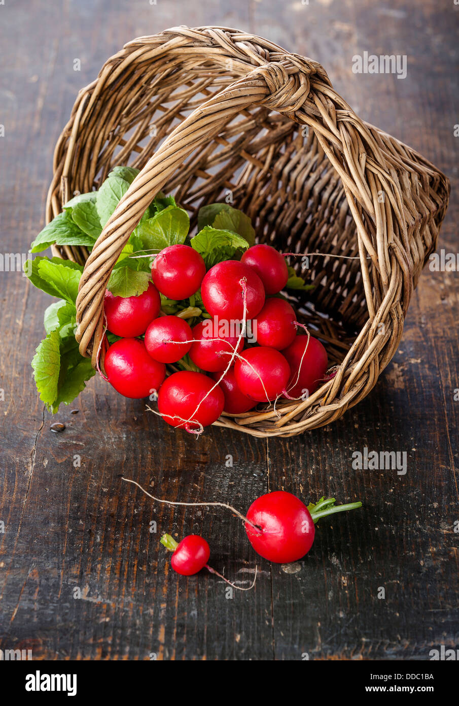 Fresh garden radish in wicker basket on wooden background - Stock Image