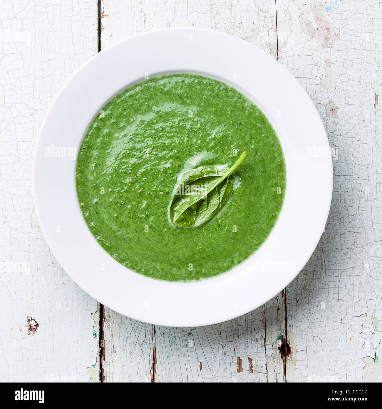Spinach soup in white bowl - Stock Image
