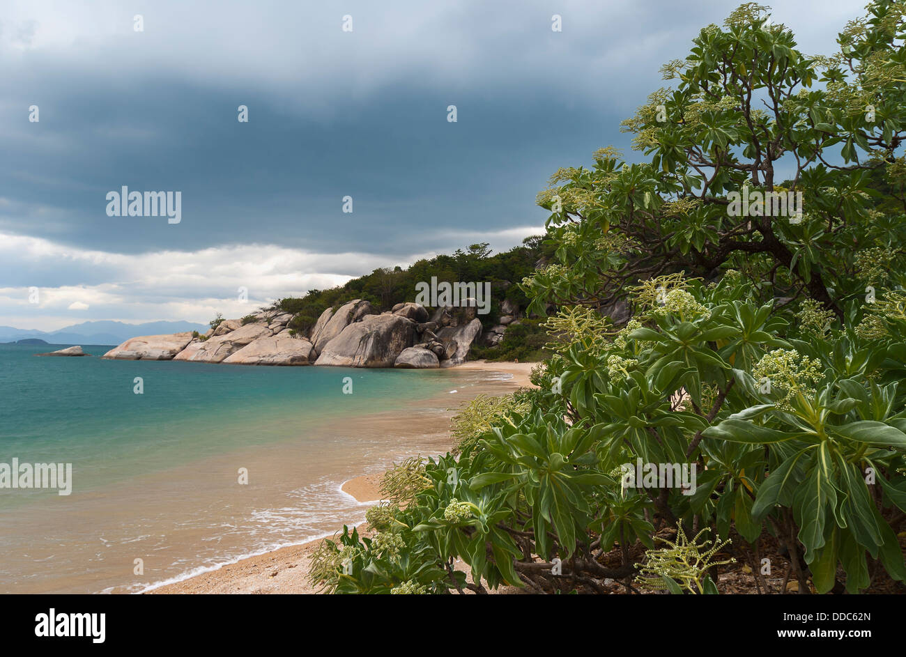 Storms gather over a tropical paradise beach. - Stock Image