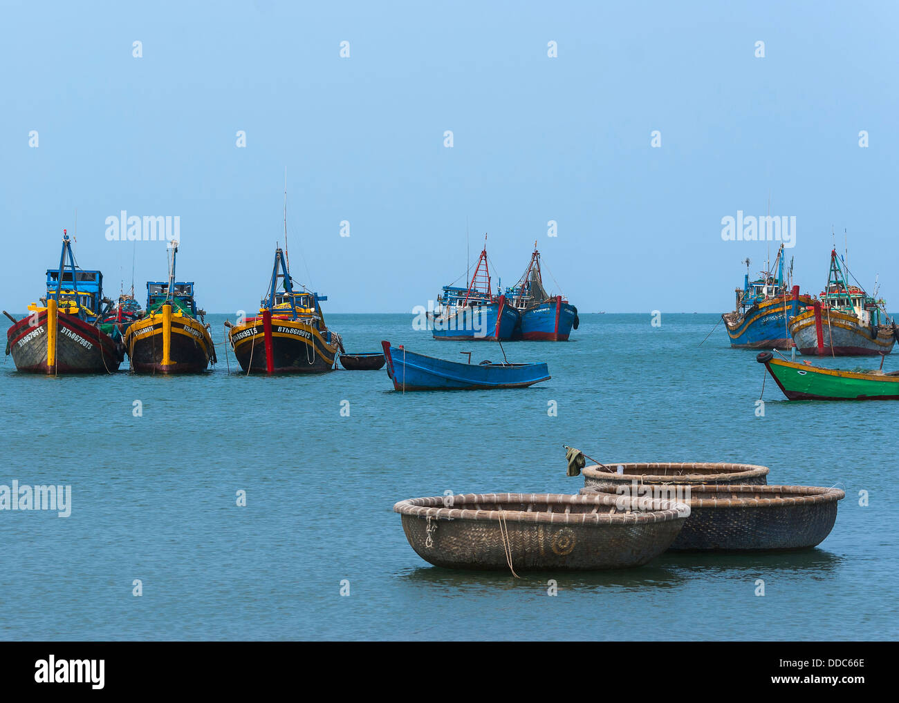A few fishing vessels float on the South China sea in front of Mui Ne village in South Vietnam. - Stock Image