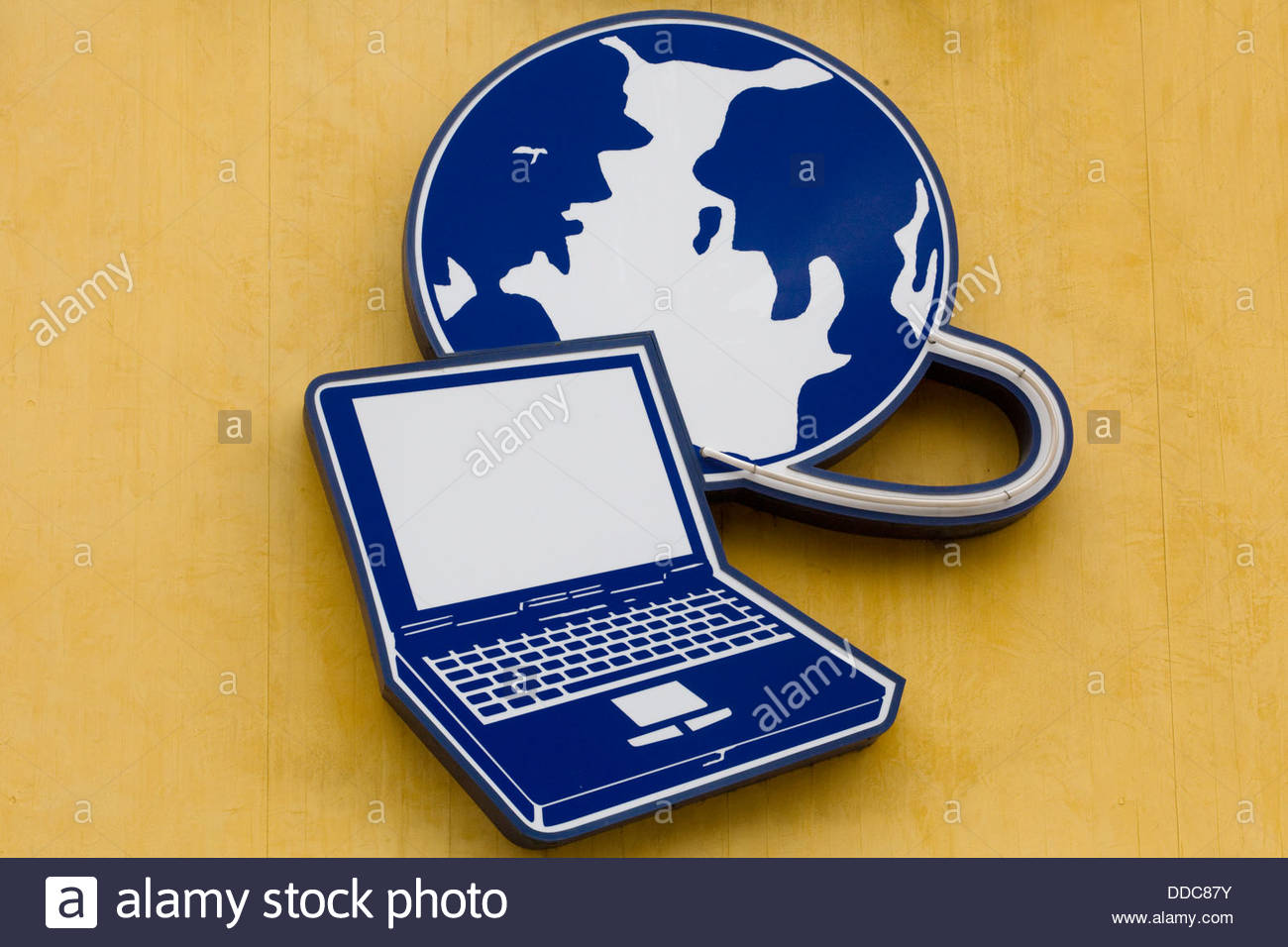 World and Laptop advertising the world wide web on yellow background - Stock Image