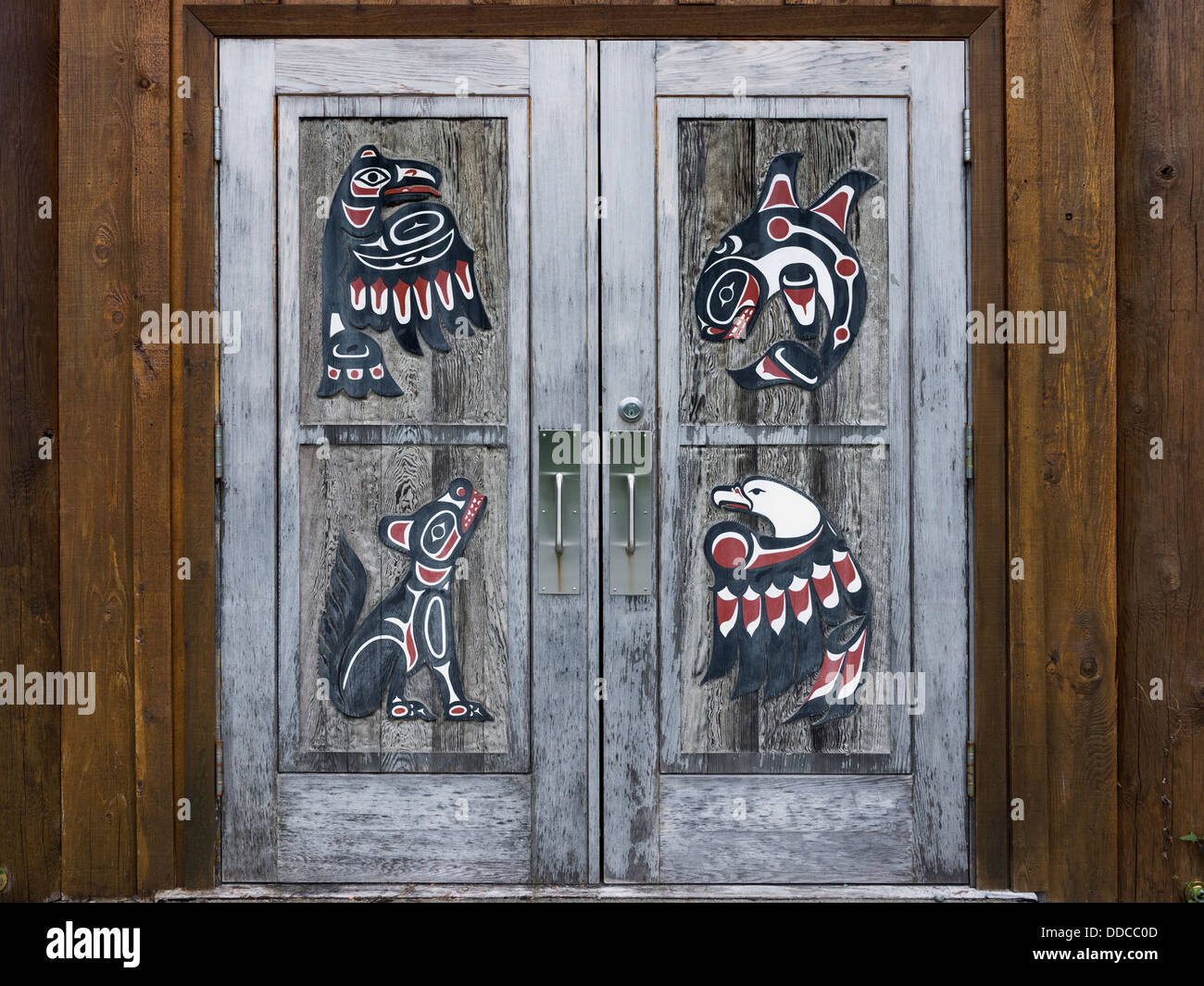Door to the Klemtu big house containing four totemic figures representing the Klemtu kinship groups. - Stock Image