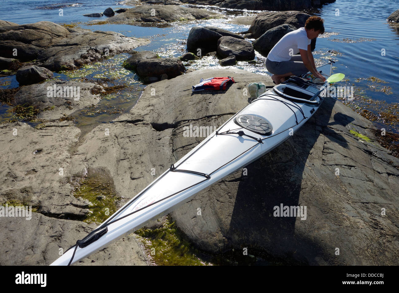 A woman packs her kayak for a tour - Stock Image