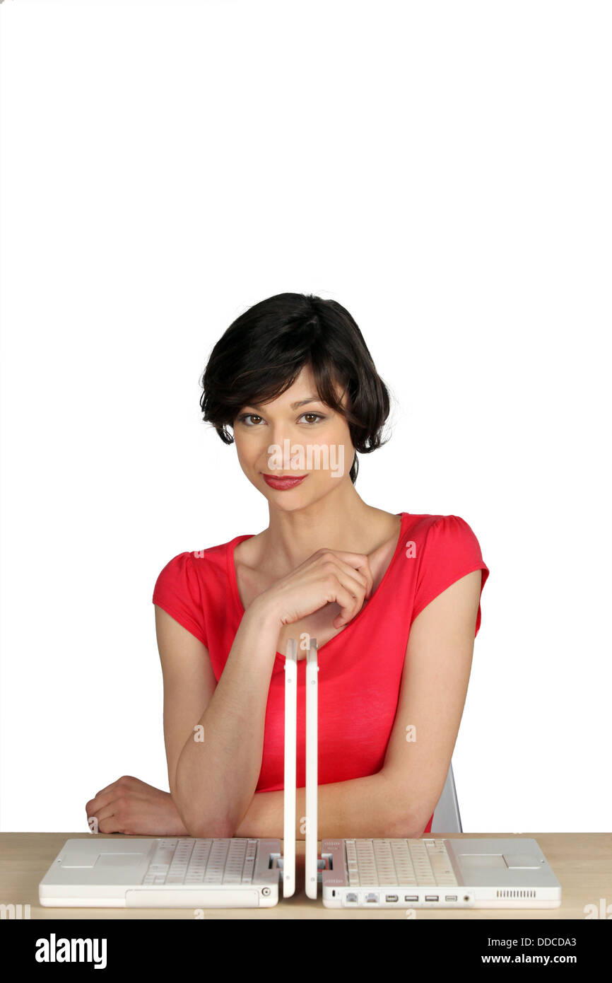 Woman behind two laptops - Stock Image