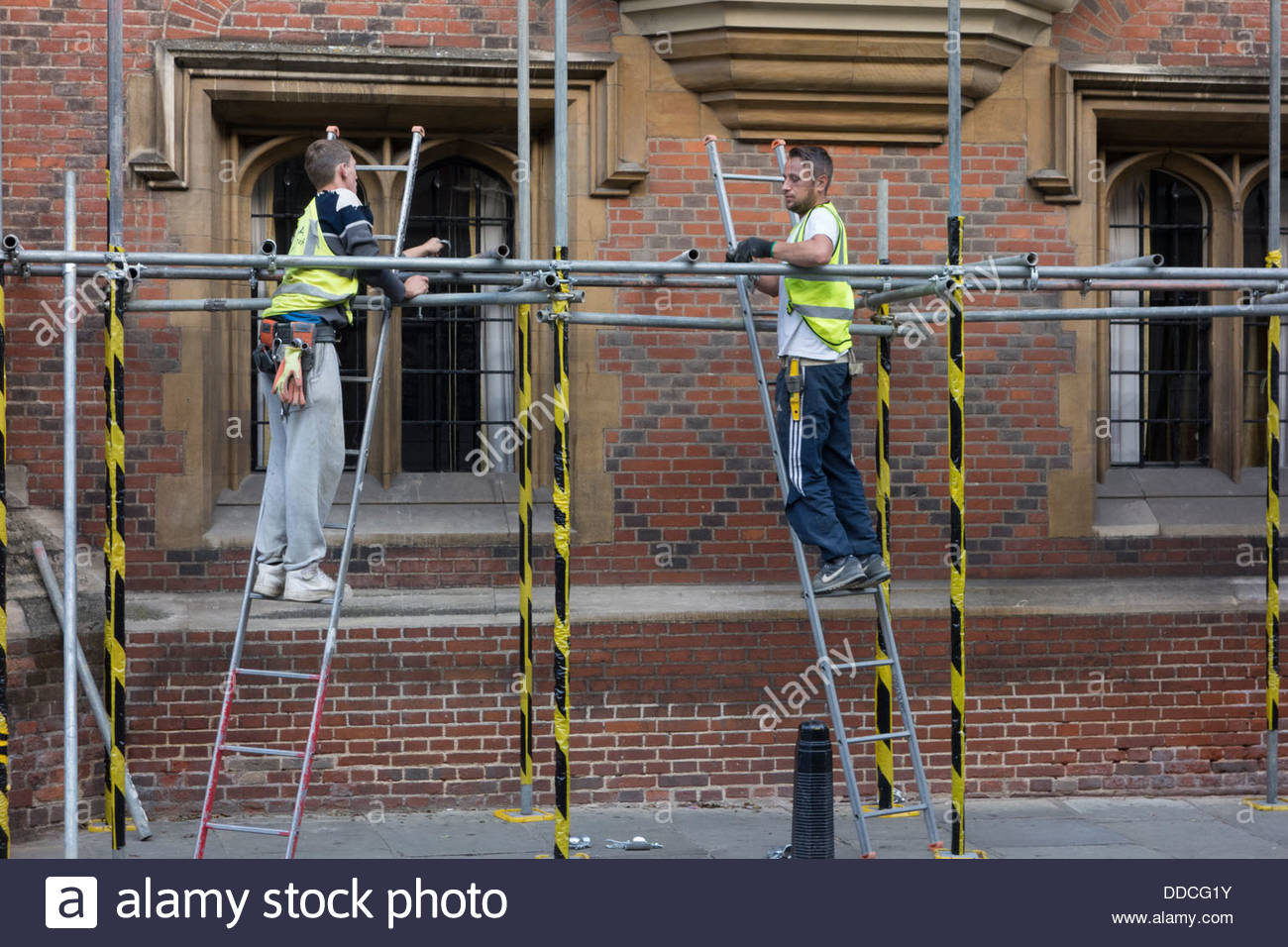 Scaffolders installing scaffolding on a college in Cambridge - Stock Image