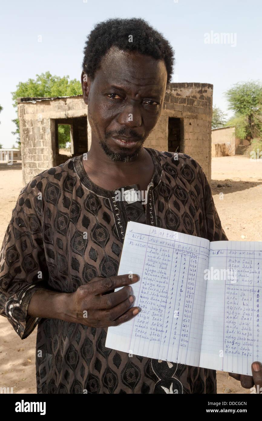 Storeroom Steward Shows Inventory Book at Bijam, a Wolof Village, near Kaolack, Senegal. - Stock Image
