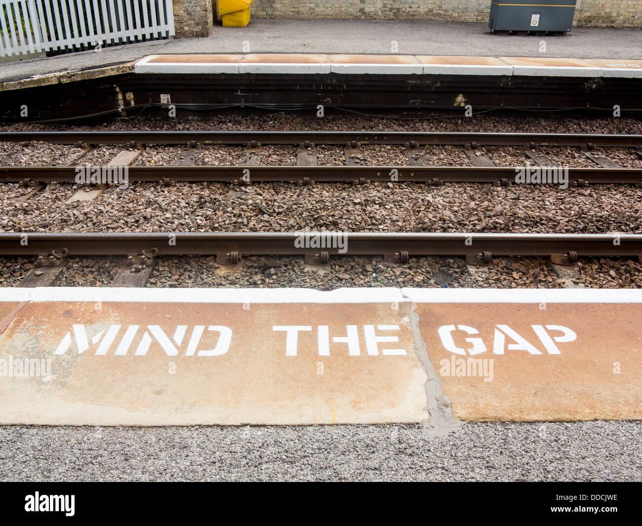 Mind the gap sign on railway station platform - Stock Image