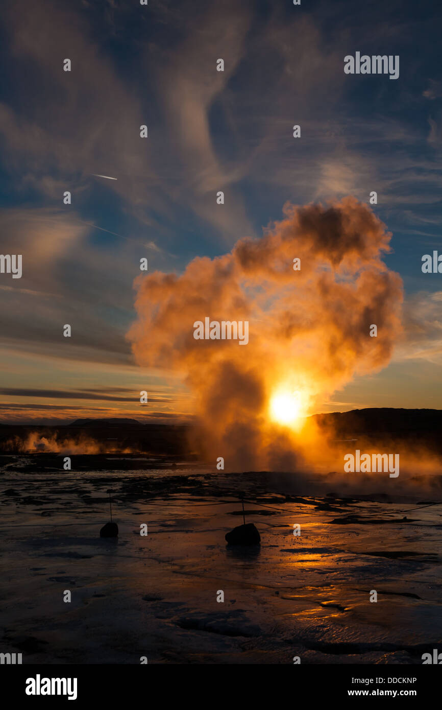 Low winter sun shines through the last gasp of steam at Geysir, Iceland - Stock Image