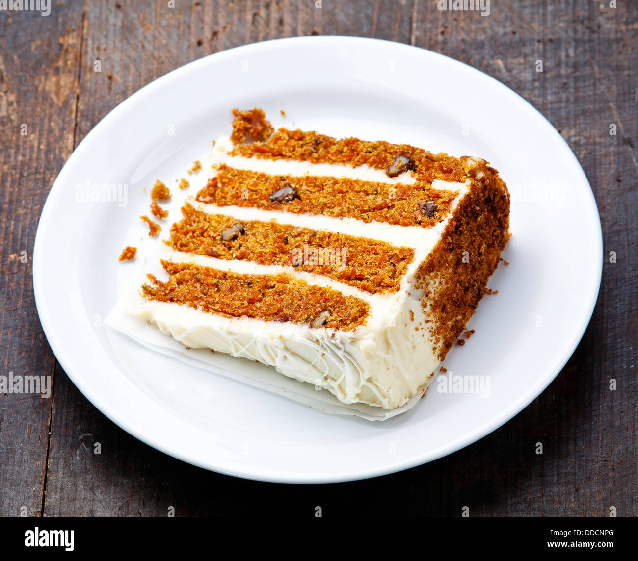 Slice of carrot cake on wooden background - Stock Image