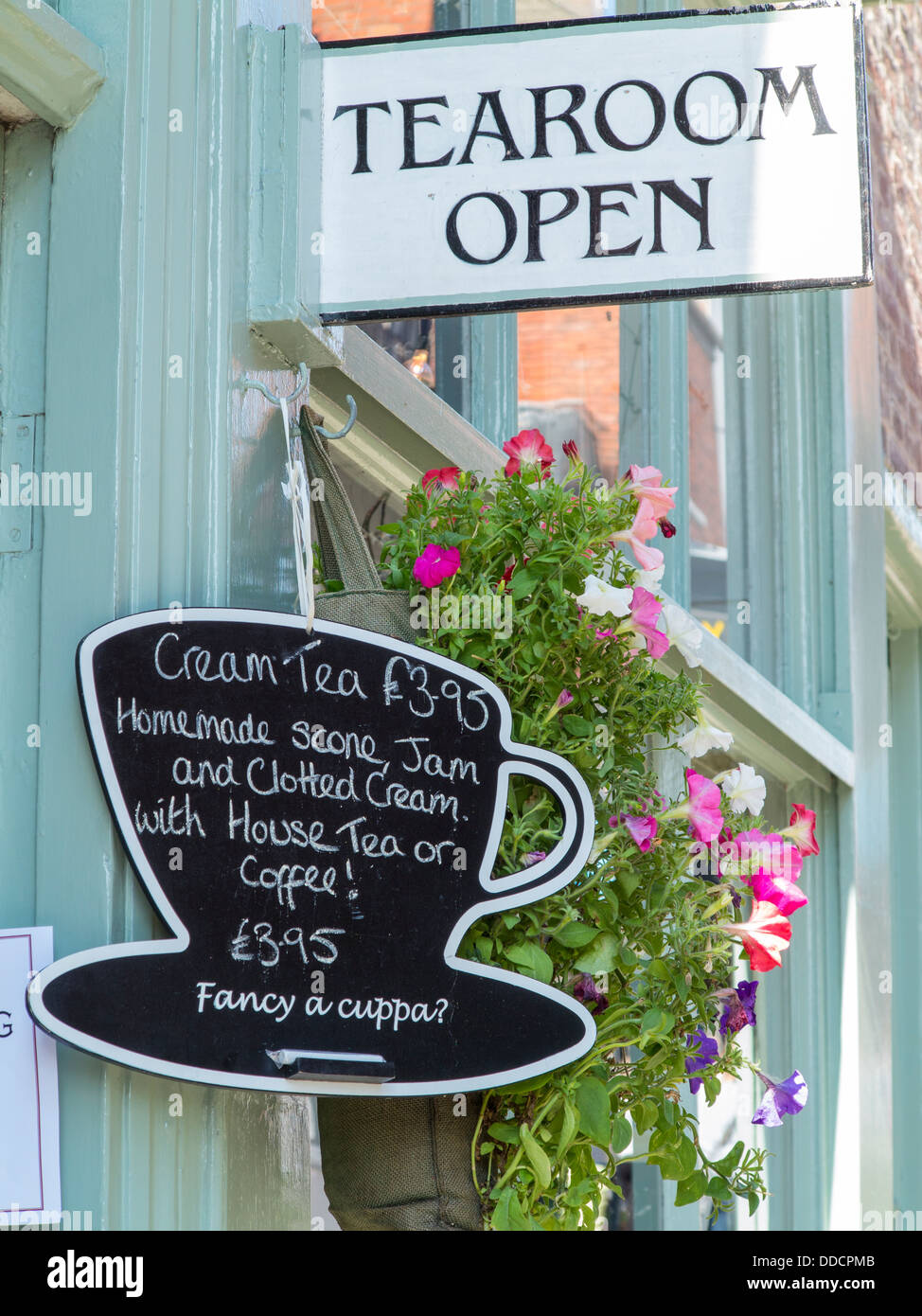 Tearoom with cup and saucer blackboard sign offering cream tea with scones and clotted cream, Steep Hill, Lincoln - Stock Image
