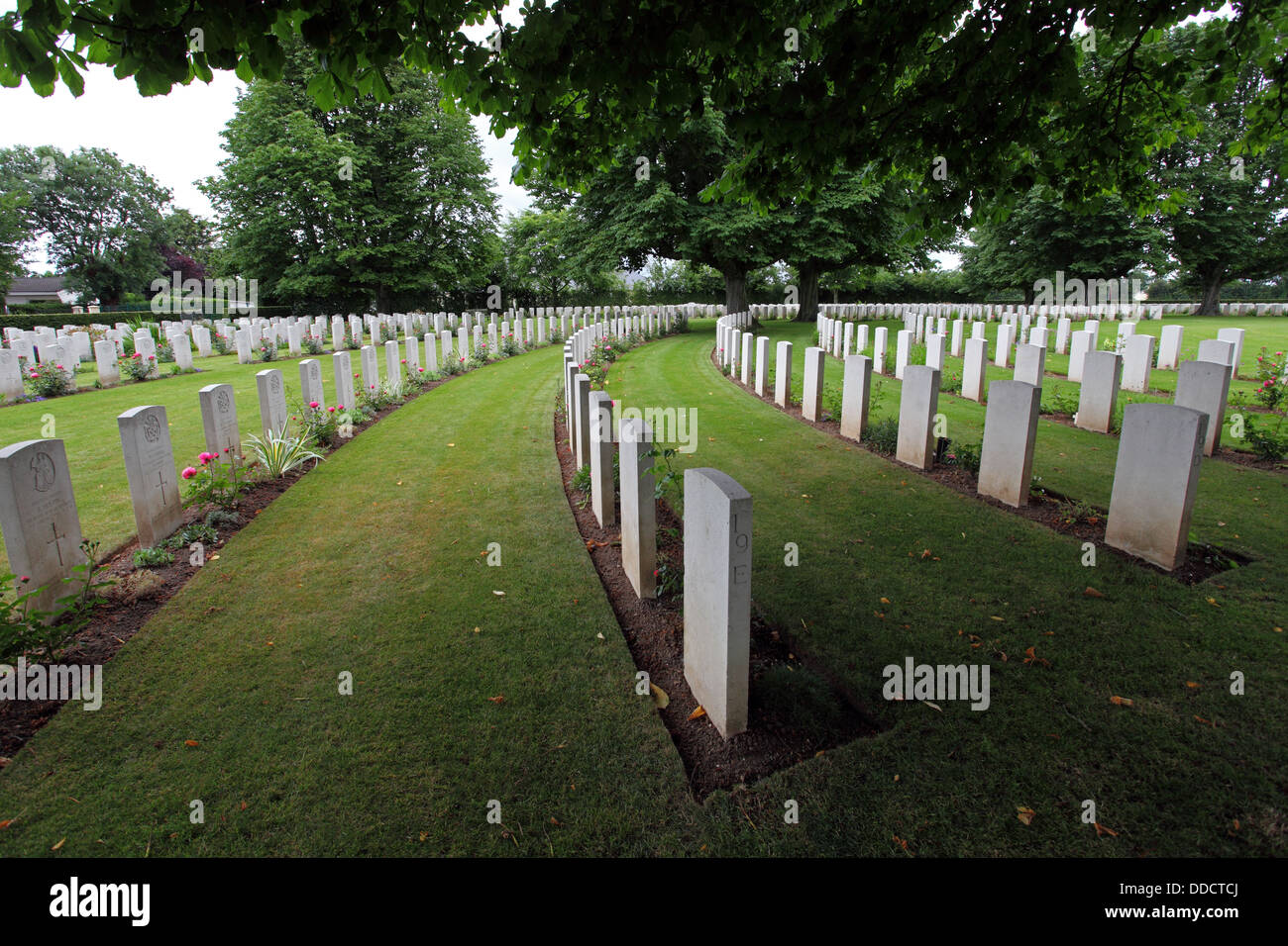 Ranks of Gravestones in a curve under trees in the British cemetery, Bayeux, Normandy France Stock Photo