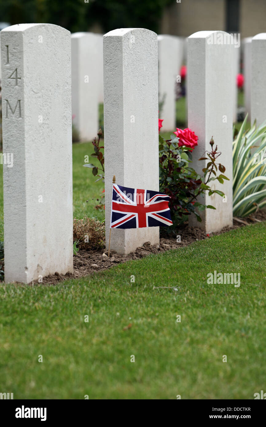 British flag flying at the base of a grave in the British Cemetery, Bayeux, Normandy, France Stock Photo