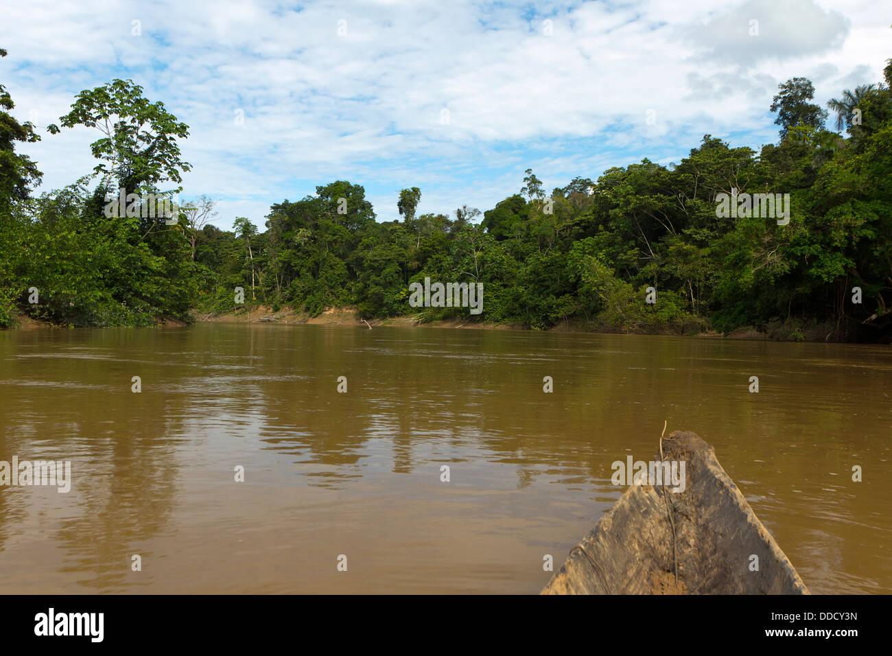 Drifting down the Rio Cononaco, deep in the Ecuadorian Amazon in a dugout canoe - Stock Image