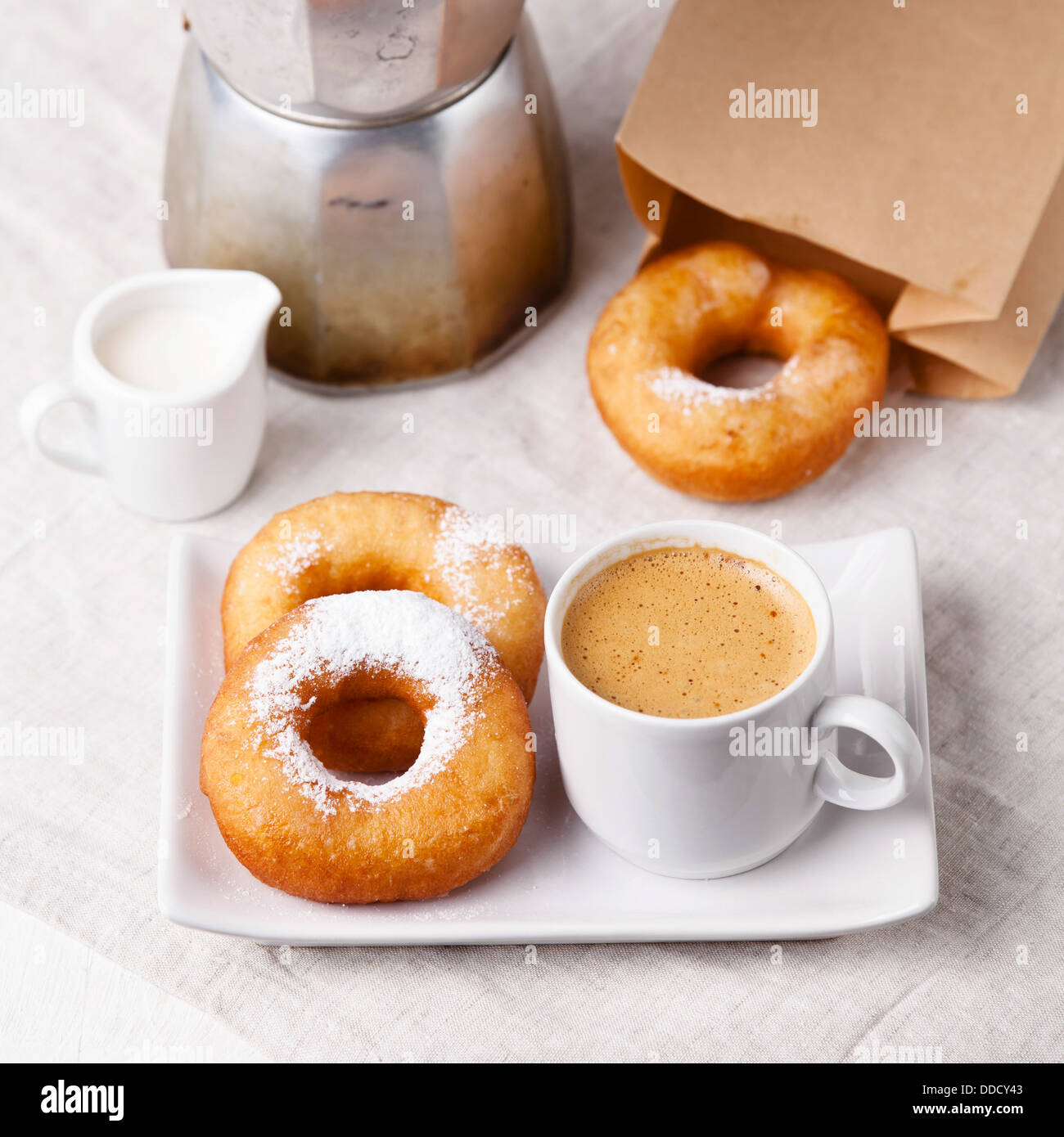 Donuts and coffee on morning breakfast table - Stock Image