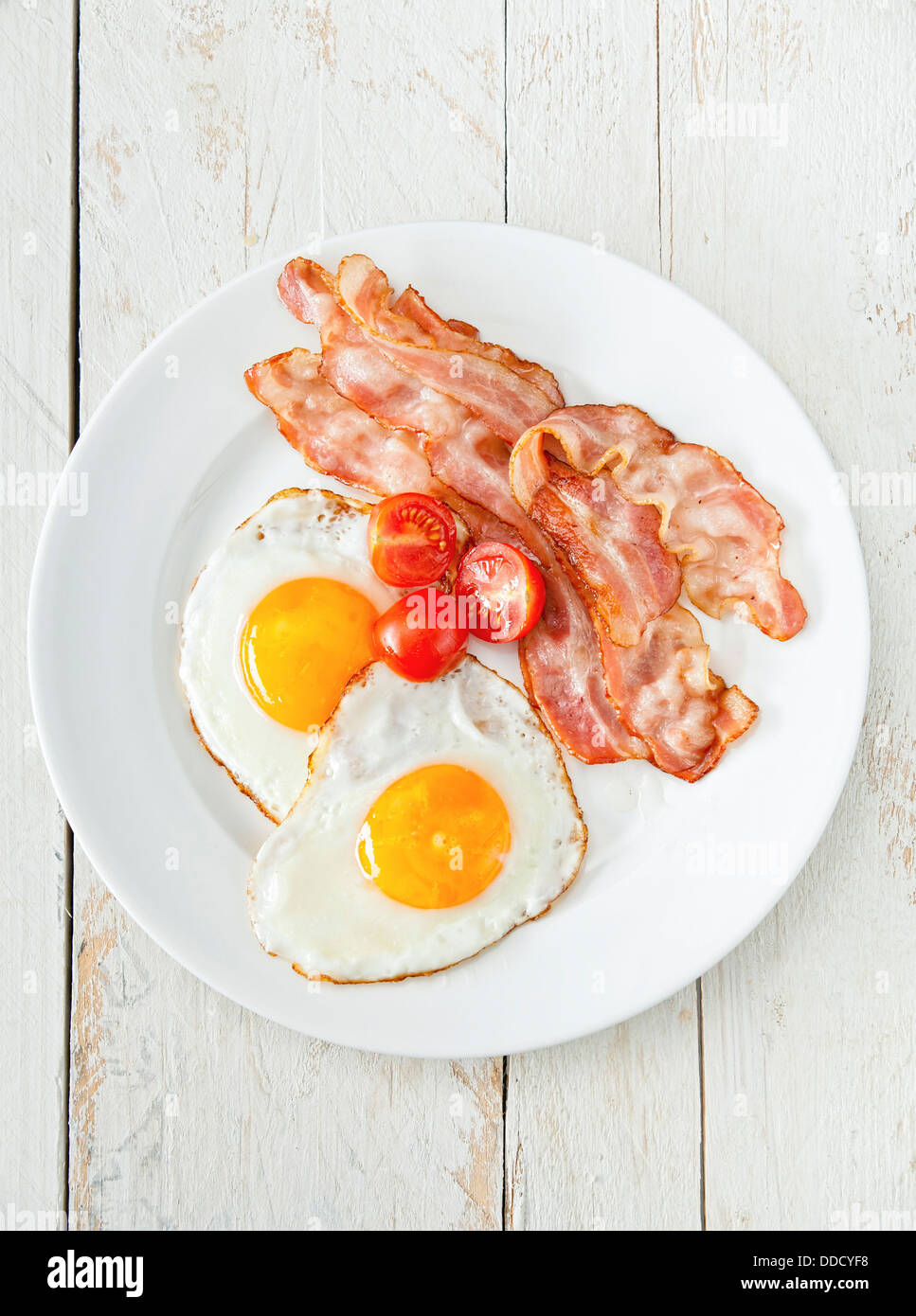 Eggs and bacon with tomato for breakfast - Stock Image