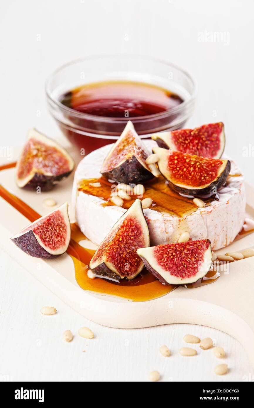 Cheese, figs and honey on light background - Stock Image