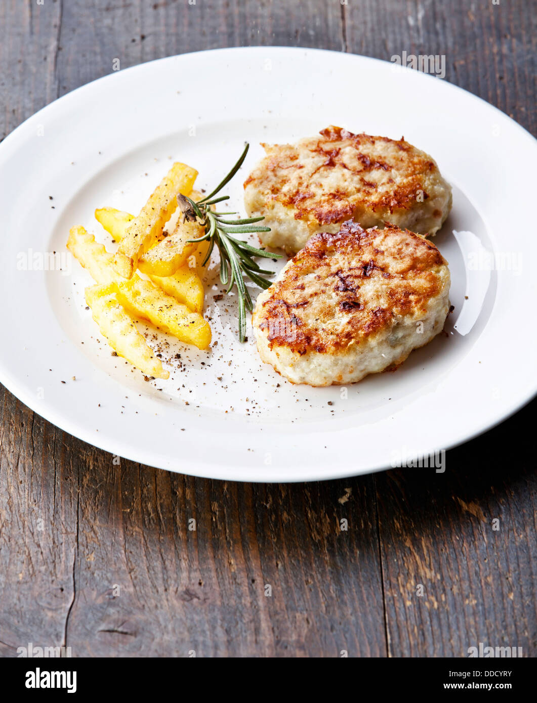 Fishcakes with french fries and herbs - Stock Image