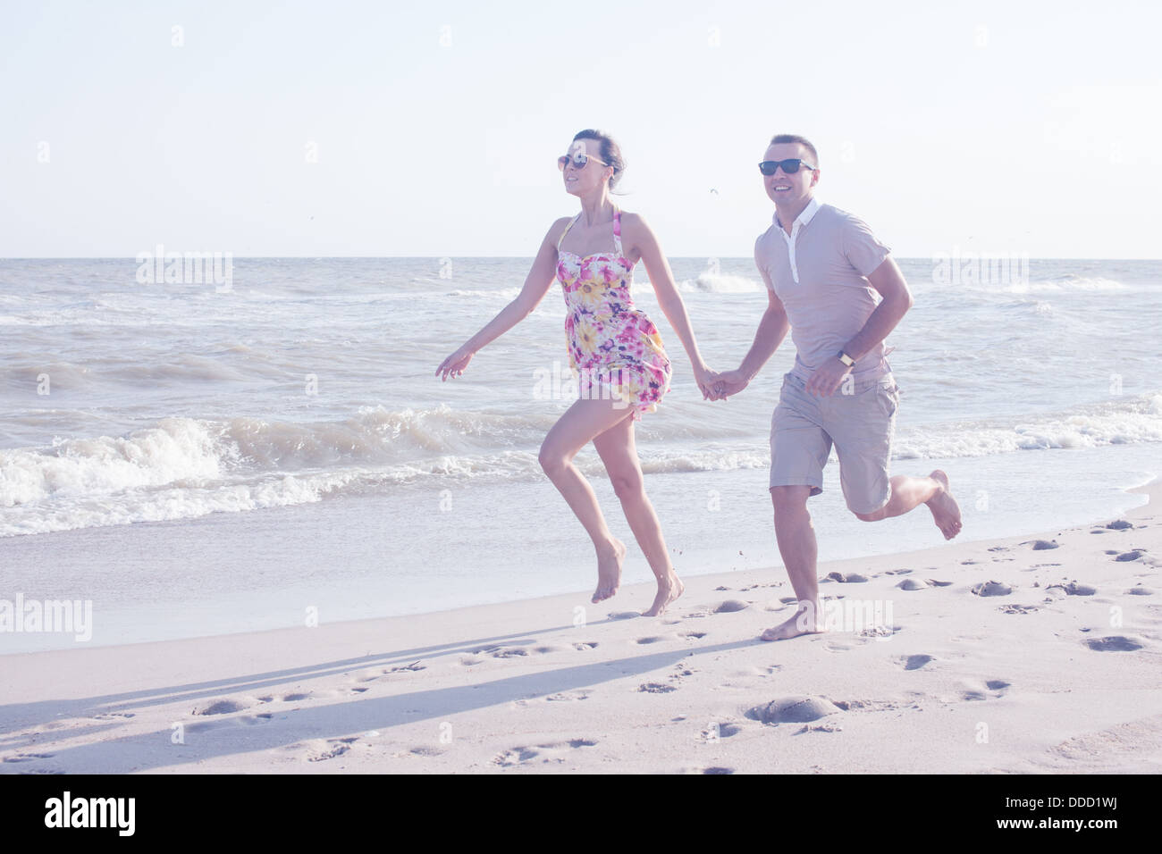 Young happy couple running together among a seashore at sunny day. Casual clothes - Stock Image