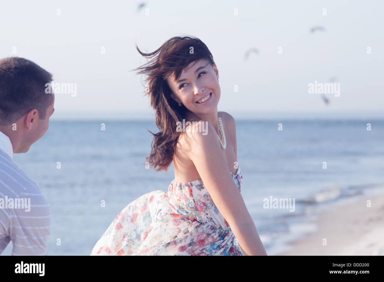 Beautiful Girl running from her boyfriend during summer time fun on the seashore - Stock Image