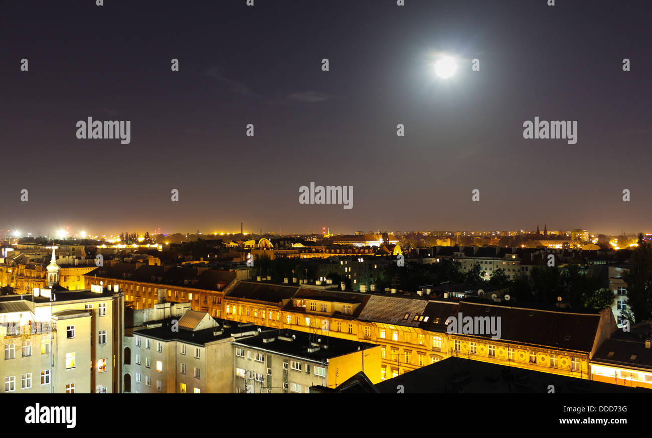 rooftops of old houses at night with the moon shining - Stock Image