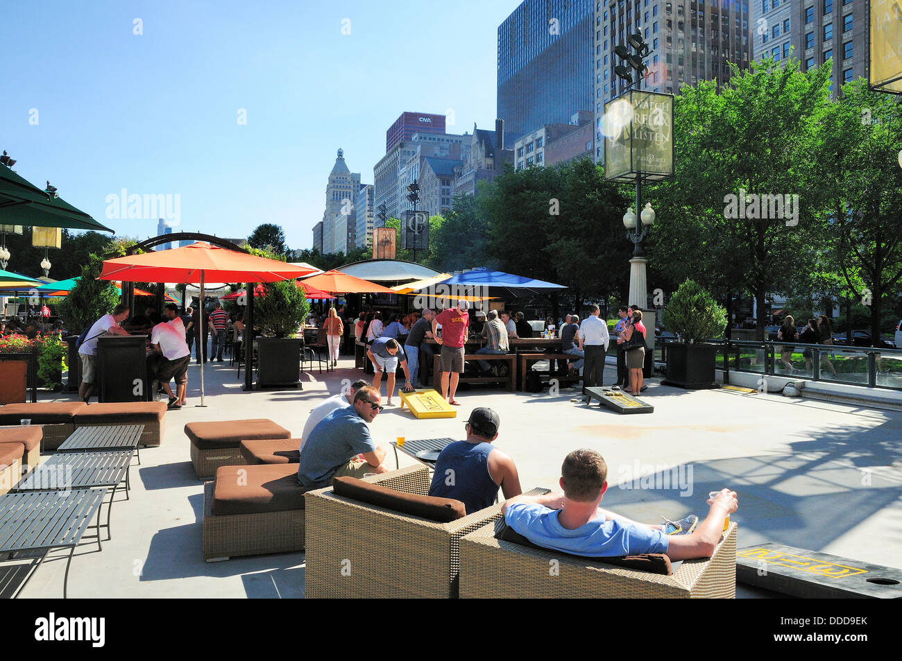 View of Chicago's Park Grill at Millennium Park. Young men watching a game of bean bag toss while lounging. - Stock Image