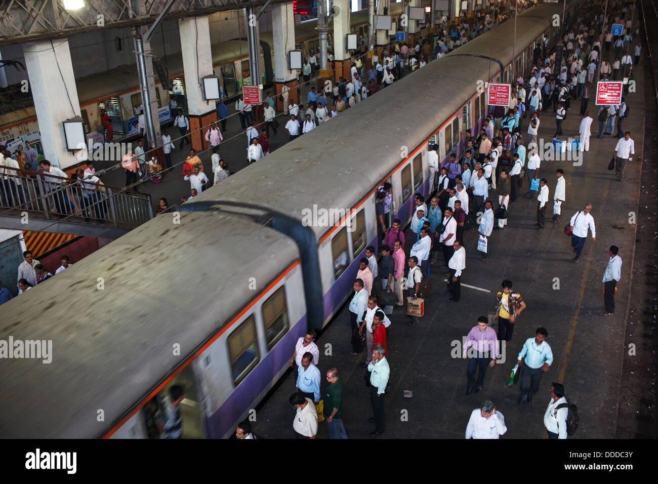 Passengers and trains at crowded Chhatrapati Shivaji Terminus (Victoria Terminus) railway station in Mumbai, India. - Stock Image