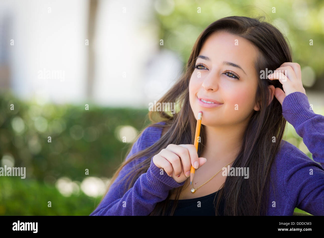 Attractive Pensive Mixed Race Female Student with Pencil Sitting on Campus Bench. - Stock Image