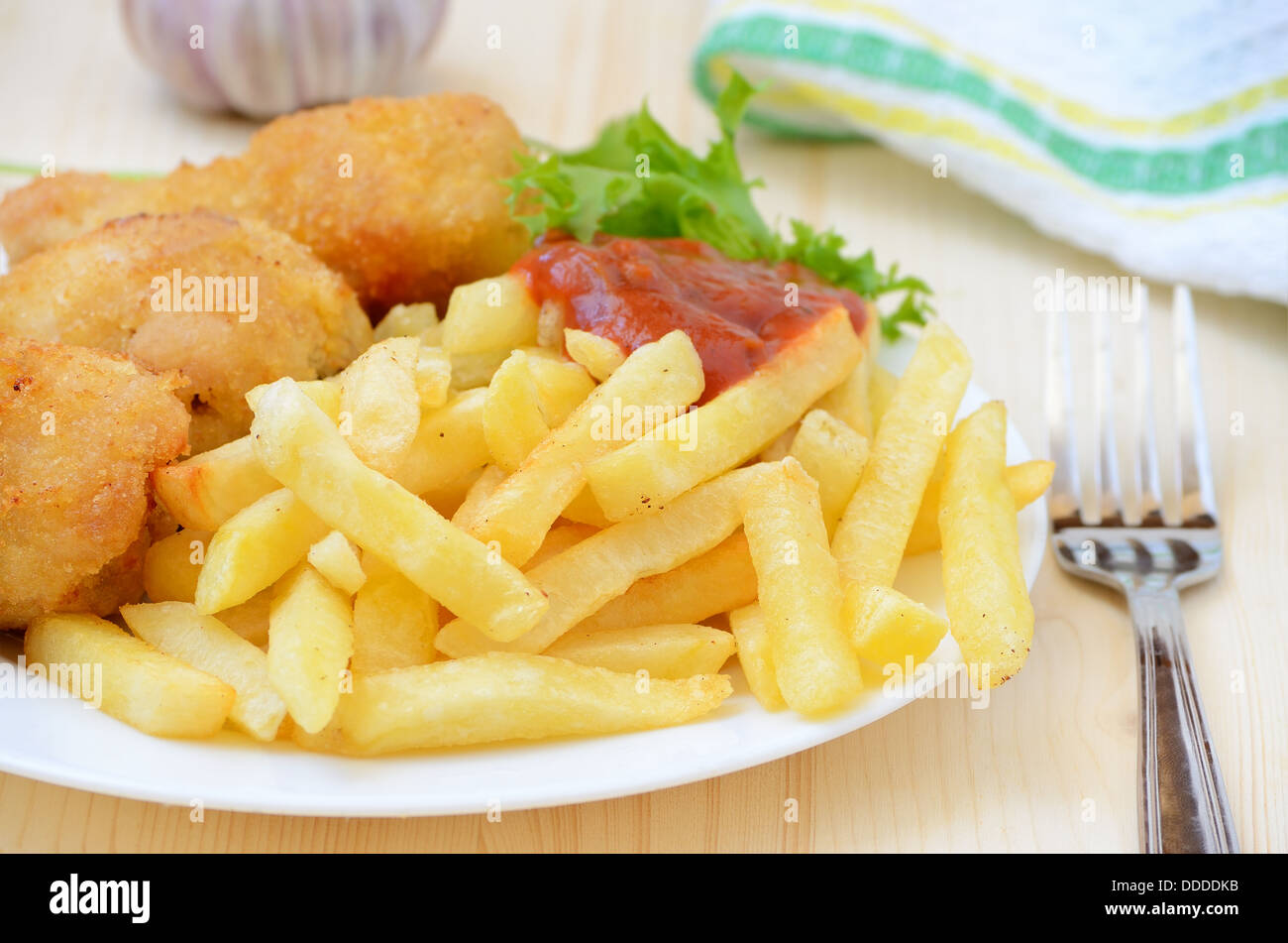 Fried chicken with french fries on wooden table - Stock Image