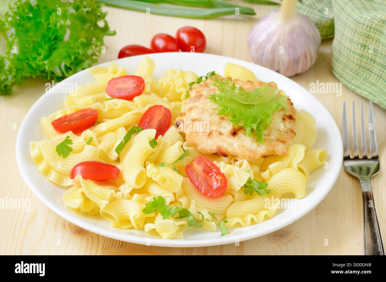 Pasta with tomatoes and chicken cutlet on white plate on the wooden table - Stock Image