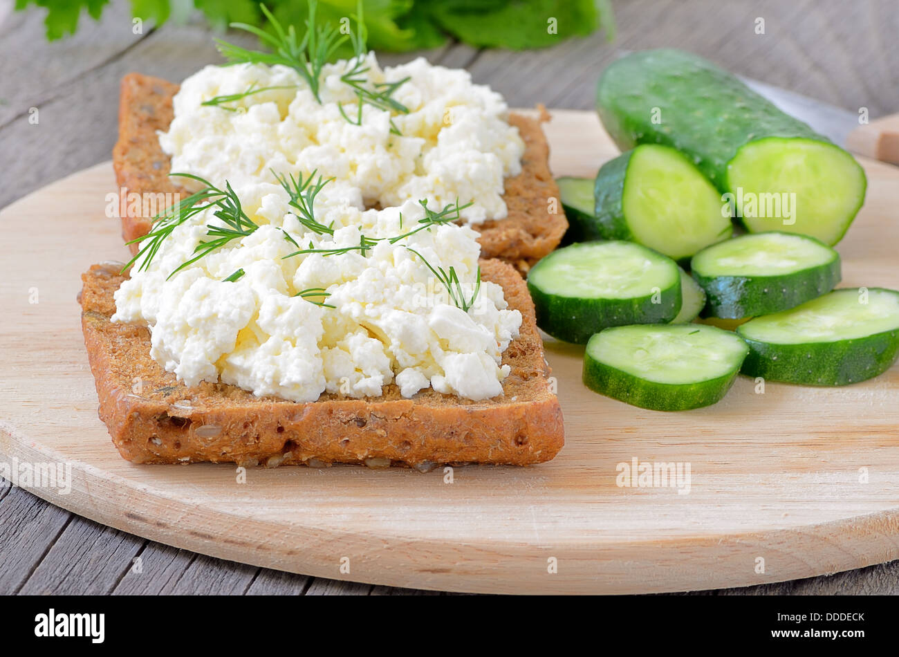 Sandwiches with curd cheese and cucumber slices on wooden cutting board. - Stock Image
